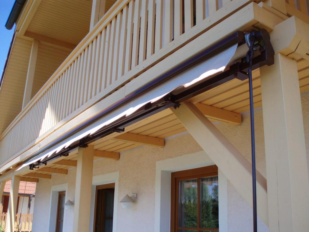 Detail ukotvení markýzy pod dřevěným balkonem