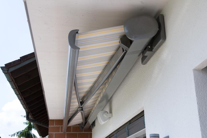 Výsuvná markýzy instalovaná pod střechou domu