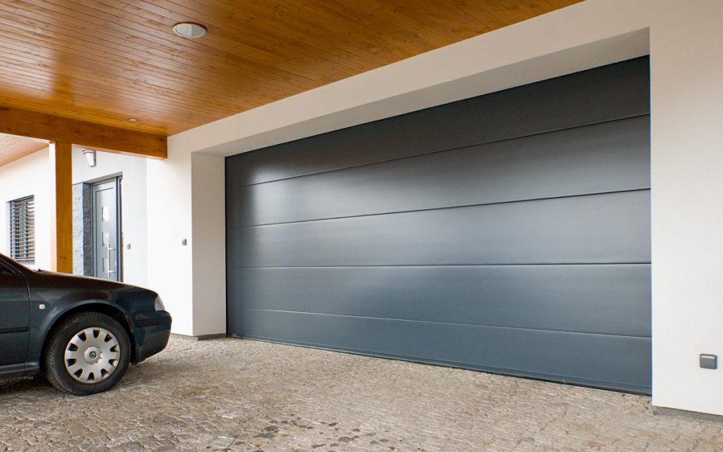 Antracitová barva garážovým vratům sluší. Výborně se hodí k hliníkovým oknům a dveřím.