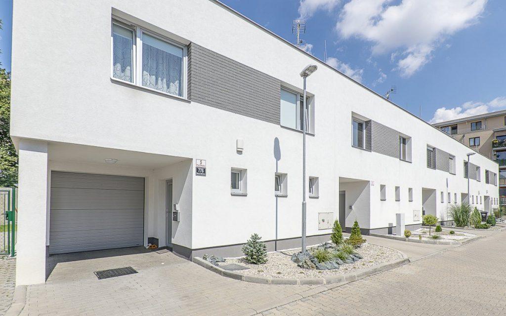 Stříbrná garážová vrata fungují jako designový prvek domu