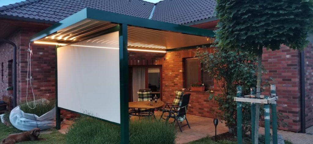Pergola Artosi s LED osvětlením a bočním stíněním vykouzlí útulné zákoutí i v podvečer.